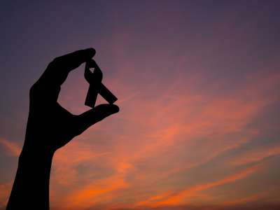 Person holding ribbon against sunset sky