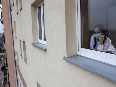 woman with mask looks out window of apartment building